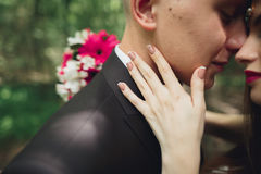 Beautiful young wedding couple is kissing and smiling in the park Royalty Free Stock Photos