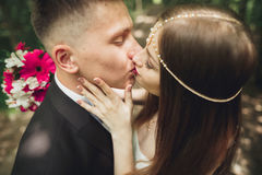 Beautiful young wedding couple is kissing and smiling in the park Stock Images