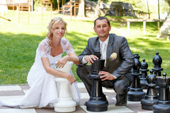 Beautiful young wedding couple and outdoor chess Stock Image