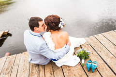 Beautiful young wedding couple sitting on the pier Stock Photography