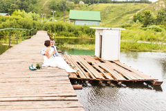 Beautiful young wedding couple sitting on the pier Stock Photos