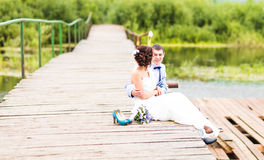 Beautiful young wedding couple sitting on the pier Stock Image