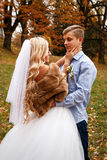 Beautiful young wedding couple stand happy together in a park in Stock Photo