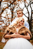 Beautiful young wedding couple stand happy together in a park in Royalty Free Stock Photo