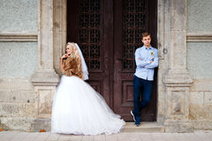 Beautiful young wedding couple stand happy together in a park in Stock Photos