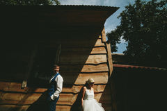 Beautiful young wedding couple stands near house Stock Photo