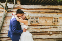 Beautiful young wedding couple stands near house Stock Photos