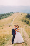 Beautiful young wedding couple walking on trail across golden sunny field with forest hills as background royalty free stock photos