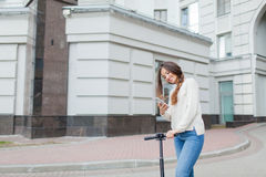Beautiful, young, and white-toothed girl with long brown hair stopped while riding the scooter, to write to a friend on the phone. She is dressed in a white Stock Photo