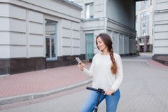 Beautiful, young, and white-toothed girl with long brown hair stopped while riding the scooter, to write to a friend on the phone. She is dressed in a white Royalty Free Stock Photography
