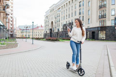 Beautiful, young, and white-toothed girl with long brown hair stopped while riding the scooter, to write to a friend on the phone. She is dressed in a white Royalty Free Stock Photos