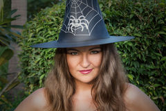 Beautiful young witch with green eyes and hat outdoors Stock Photos