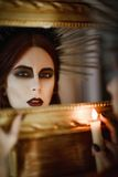 Beautiful young witch holding candle in hand and looking into mirror Royalty Free Stock Image