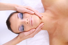 Beautiful young woman. Receiving facial massage royalty free stock photos