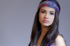 Beautiful Young Woman. Wearing a purple bandanna on a gray background stock image