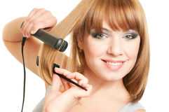 Beautiful young woman. Portrait of beautiful young woman with fashion hairstyle holding crimper and comb Stock Photo