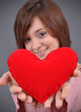 The beautiful young woman. Holds in hands a red heart on a grey background. Selective focus on heart Stock Images
