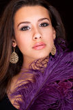 Beautiful Young Woman. Beautiful and exotic young mixed race woman covered by a long purple feather on a black background Stock Photos