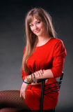 Beautiful young woman. In red dress sitting on a chair on a gray background stock photos