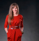 Beautiful young woman. In red dress on a gray background stock images