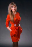 Beautiful young woman. In red dress on a gray background royalty free stock images