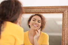 Beautiful young woman with acne problem. Looking in mirror at home Stock Photo