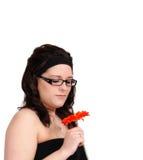 Beautiful young woman admiring a flower closeup Stock Photography