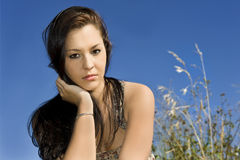 Beautiful young woman against blue sky Royalty Free Stock Images