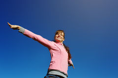 Beautiful young woman against the blue sky. Beautiful young woman with arms raised against the blue sky Royalty Free Stock Image