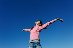 Beautiful young woman against the blue sky. Beautiful young woman with arms raised against the blue sky Stock Image