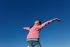 Beautiful young woman against the blue sky. Beautiful young woman with arms raised against the blue sky Stock Photography
