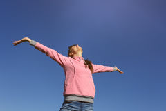 Beautiful young woman against the blue sky. Beautiful young woman with arms raised against the blue sky Stock Photo