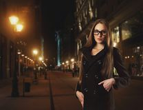 Beautiful young woman against a city by night Stock Photo