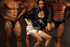 Beautiful young woman against three athletes Stock Images