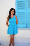 Beautiful young  woman against white greece house with blue window Royalty Free Stock Photos