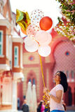 Beautiful young woman with air balloons on the city street. Beautiful young woman with air balloons walking on the city street royalty free stock images