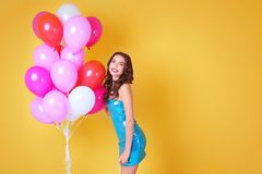 Beautiful young woman with air balloons. On yellow background royalty free stock image