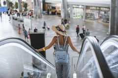 Beautiful young woman at the airport descends on an escalator in a straw hat and with a backpack. royalty free stock photo