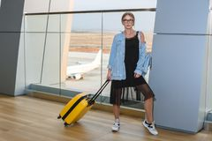 Beautiful young woman at the airport with a yellow suitcase and blue backpack. royalty free stock images
