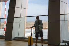 Beautiful young woman at the airport with a yellow suitcase and blue backpack. stock images