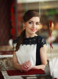 Beautiful young woman alone waiting at a table in restaurant Stock Images