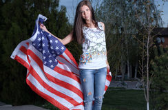 Beautiful young woman with american flag outdoors Royalty Free Stock Photos