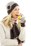 Beautiful young woman with apple, looking up. Winter style Royalty Free Stock Photos