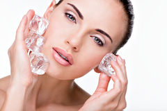 Beautiful young woman applies the ice to face Stock Photography