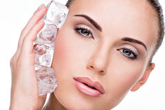 Beautiful young woman applies the ice to face Royalty Free Stock Images