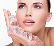 Beautiful young woman applies the ice to face Stock Photos