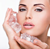 Beautiful young woman applies the ice to face Royalty Free Stock Image