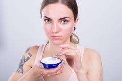 Beautiful young woman appliyng facial moisturizing cream. Royalty Free Stock Photography