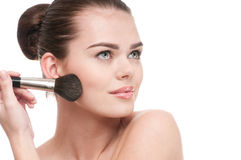 Beautiful young woman applying brush Royalty Free Stock Images