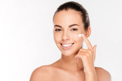 Beautiful young woman applying cosmetic cream treatment on her face Stock Photo